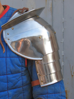 A pauldron with compound curves and lames. Note the rawhide lacing. The rawhide lace might either be part of the arming jacket, used to keep the pauldron in place, or it functions to attach the pauldron to a gorget.